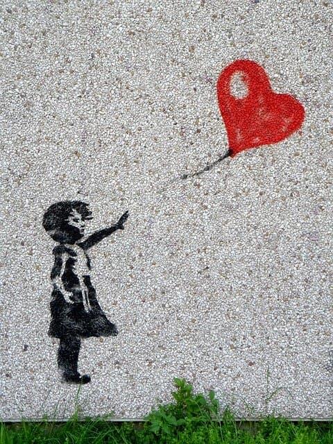 bambina sola con palloncino rosso